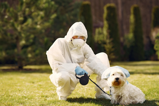 Woman in a protective suit walking with a dog