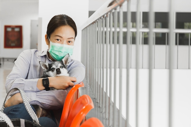 Woman in protective surgical mask holding dog protection coronavirus concept.