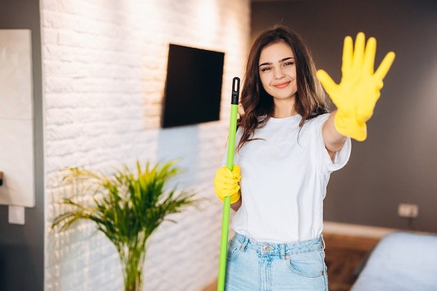 Woman in protective yellow gloves holding mop and wiping dust in her house.