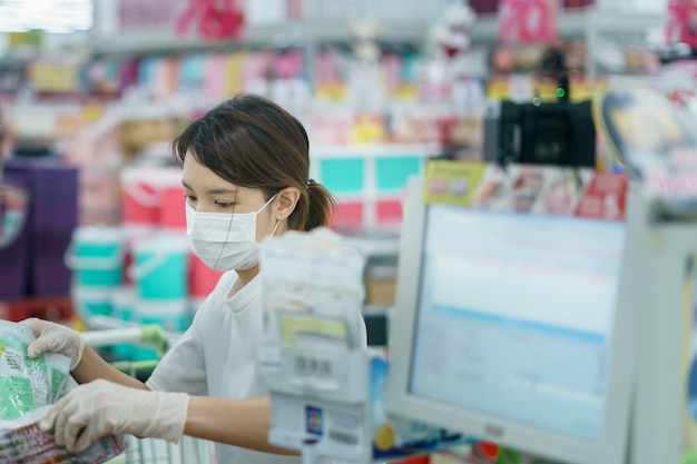 Woman protects herself from corona infection with surgical mask and gloves at cashier scanning grocery .