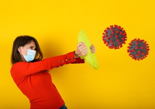Женщина защищает себя от вирусной атаки covid-19 щитом