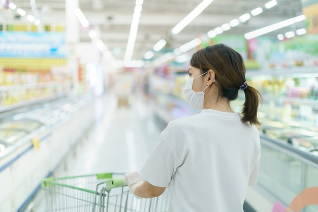Woman protects herself from infection with the surgical mask and gloves, with shopping cart for shopping at supermarket after coronavirus pandemic.