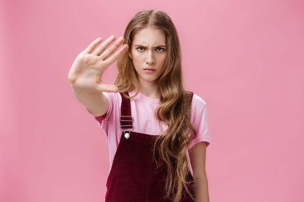 長い波状の自信に満ちた若い女の子を真剣に見ている動物で製品をテストすることに抗議する女性...