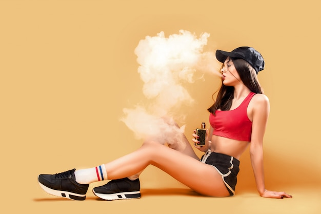 Woman puffing vapor on yellow
