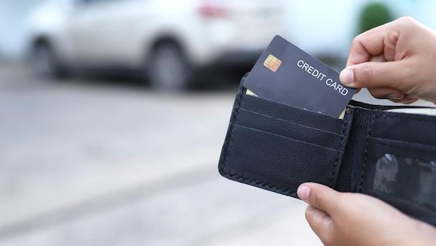 黒の財布からクレジットカードを引っ張る女性