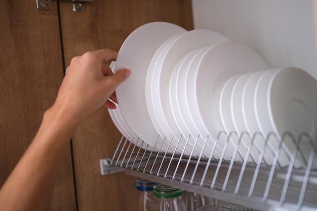 Женщина вытаскивает белую тарелку с полки на кухне крупным планом