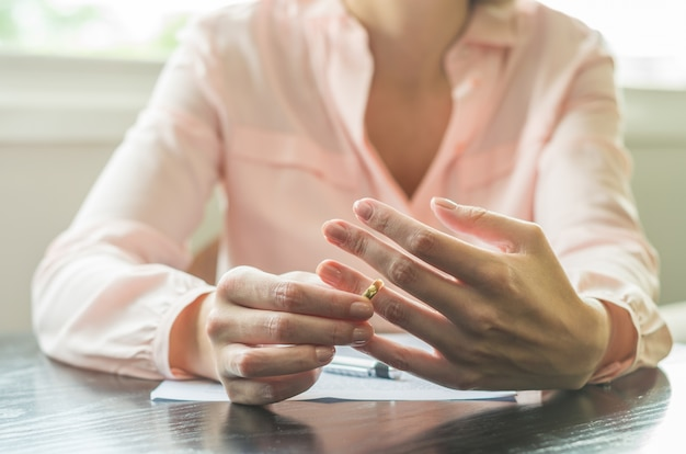 Woman pulling wedding ring from finger