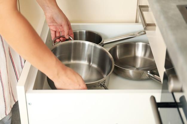 女性は台所のテーブルから鍋を引き出します。