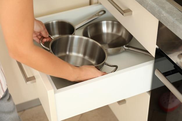 女性が台所のテーブルから鍋を引き出します。