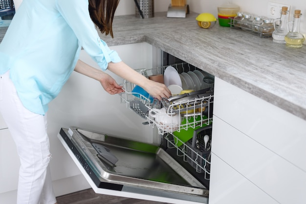 Woman pulls clean dishes from the dishwasher, close-up