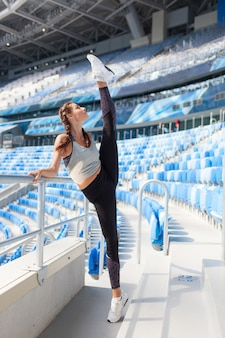 The woman pulls the leg up in stadium.
