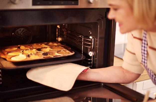 女性はオーブンからマフィンを引っ張る