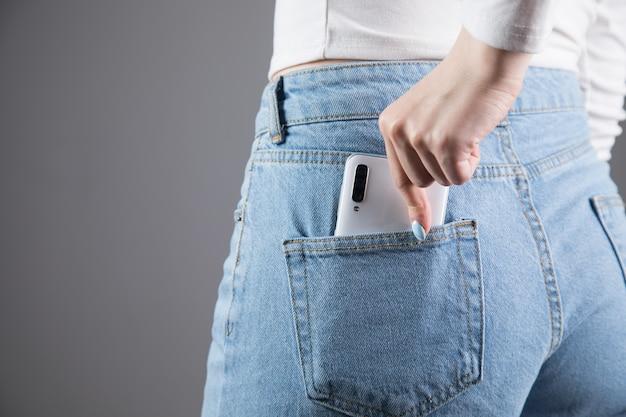女性は灰色の壁のポケットから電話を引き出します