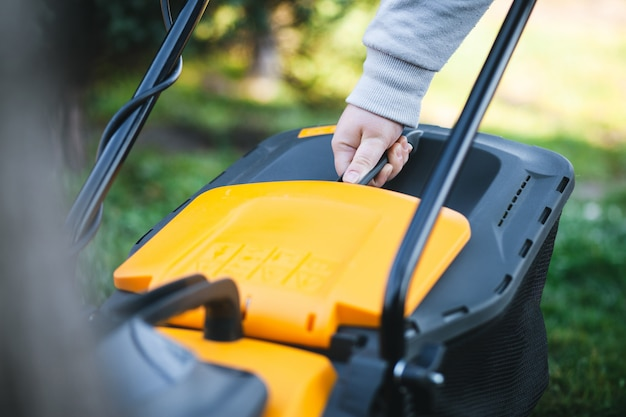 Woman pulls out a lawnmower grass catcher to empty it.