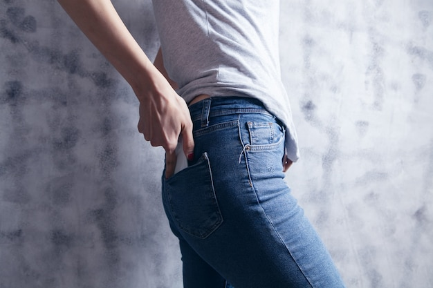 The woman pulls the phone out of the back pocket of her jeans