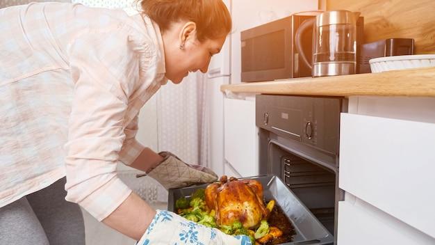 Женщина достает из духовки готовую еду, курицу с овощами