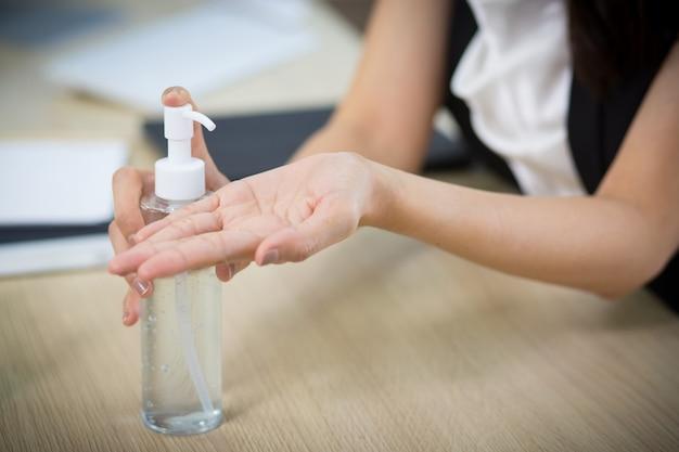 여자는 손에 씻고 항균제를 바르기 위해 알코올 젤을 펌핑합니다.