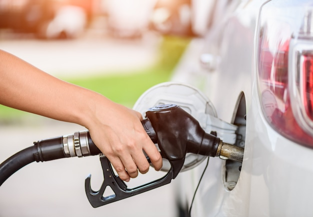 Woman pumping gasoline fuel in car at gas station