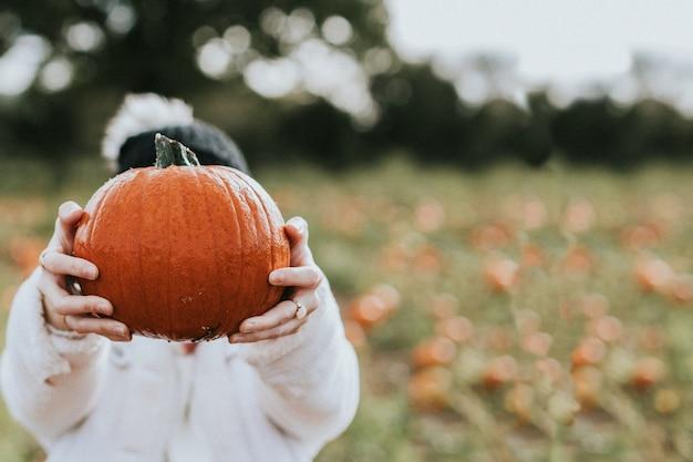 Donna in un campo di zucche prima di halloween