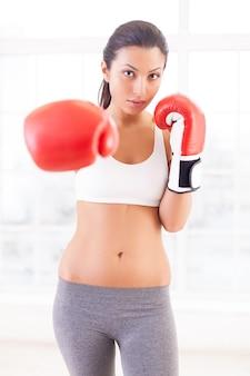 Женщина пробивает. уверенная молодая женщина в боксерских перчатках протягивает руку и смотрит в камеру