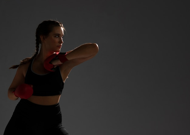 Woman punching with box gloves and copy space