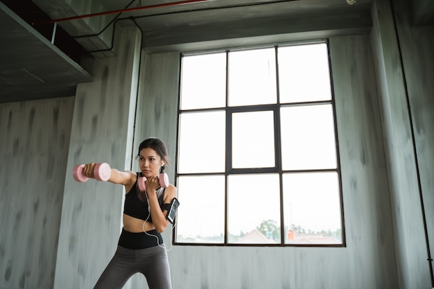 Woman punching with dumbbell on her hands