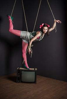 Woman puppet on tv with his hands tied posing