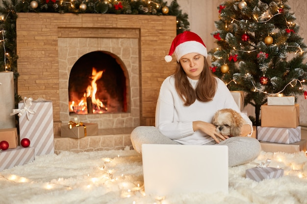 Woman and puppy dog in sweater having video call chat on laptop, enjoy christmas time at home near x-mas tree and fireplace, hugging her favorite pekingese dog, looks sad.