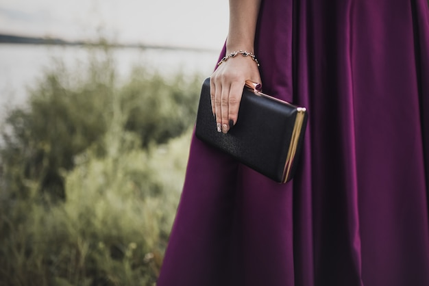 Woman in a purple satin dress and a bracelet decoration on her hand holds a clutch handbag on a green natural backgrounds a black compact clutch handbag.