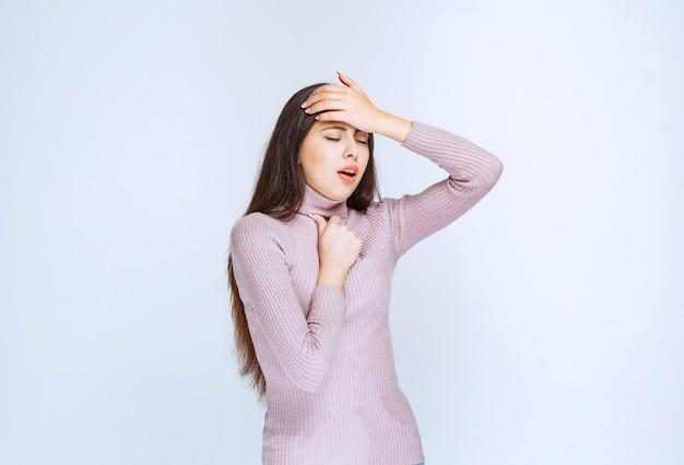 Woman in purple shirt has sore throat.
