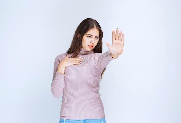Donna in camicia viola che rifiuta qualcosa con gesti di mano.