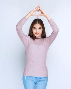 Woman in purple shirt sending love.