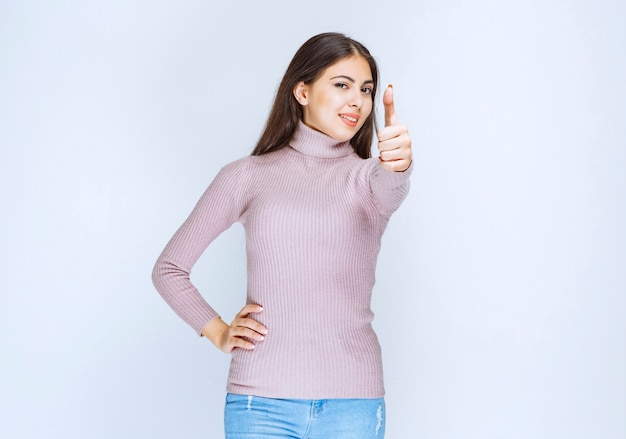 Woman in purple shirt showing enjoyment hand sign.