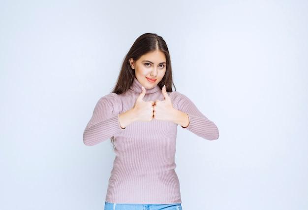 Donna in camicia viola che mostra il segno della mano di godimento.