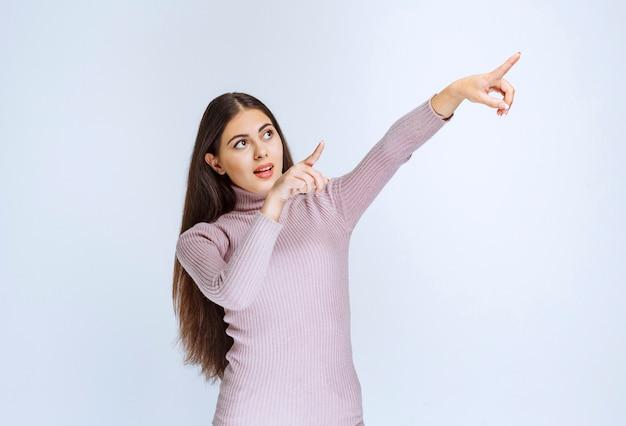 Donna in camicia viola che mostra qualcosa sopra.