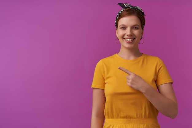 Woman on purple wall wearing yellow t-shirt and black bandana emotion smiling at you happy show to the left look interesting pointing finger aside