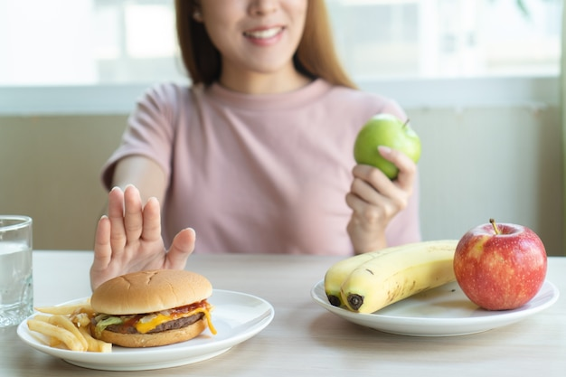 Женщина отталкивает фаст-фуд и выбирает яблоко