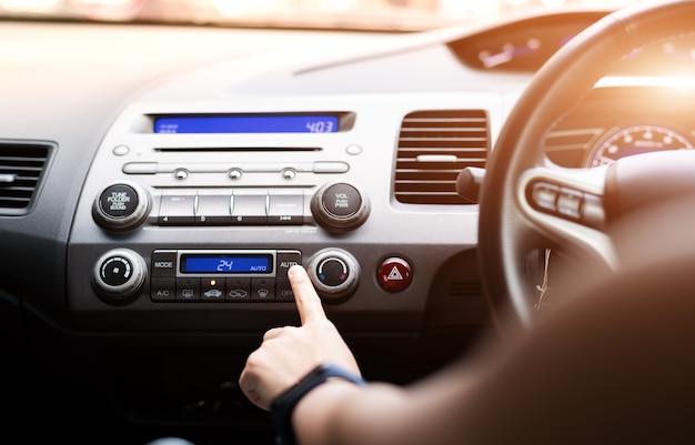 Женщина нажимает на кондиционер в автомобиле