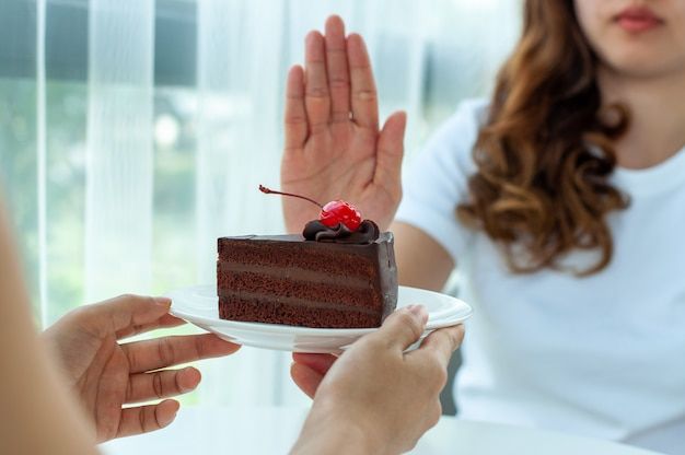 Woman pushes the plate with a chocolate cake