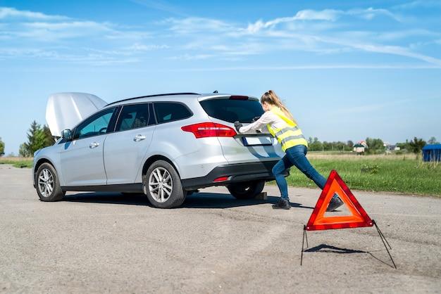 Женщина толкает свою сломанную машину на обочине дороги