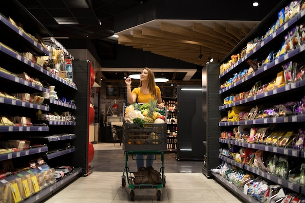 Woman pushing shopping cart between shelves in supermarket