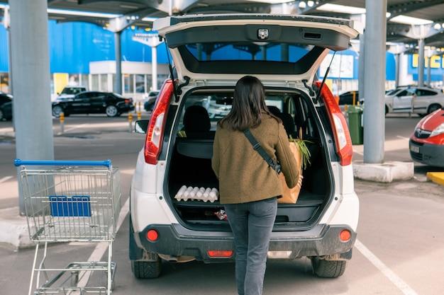 食料品店のコピースペースの後、女性が車のトランクに商品の入ったバッグを入れました