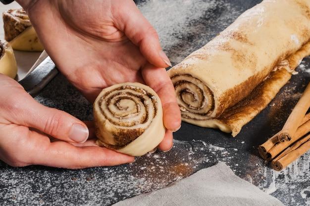 Женщина кладет на сковороду тестовые рулеты и готовит булочки с корицей для выпечки. Premium Фотографии