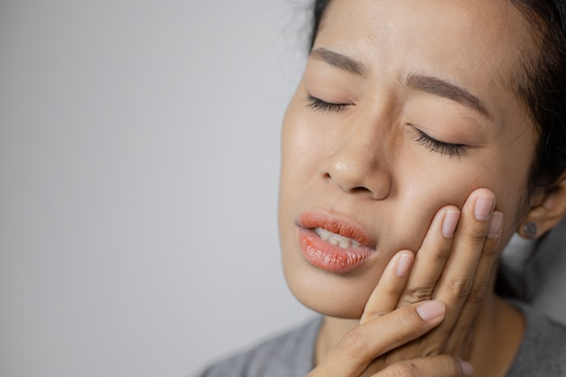 女性は歯痛のために頬に手を置いた。