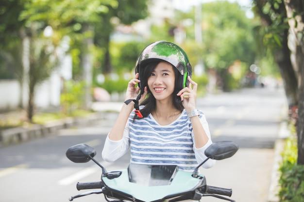 バイクに乗る前にヘルメットをかぶる女性