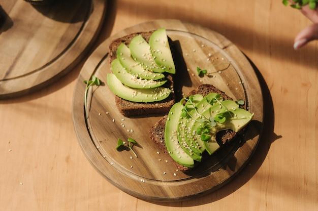 Женщина положила саженцы горчицы на бутерброд с авокадо и темным ржаным хлебом, приготовленным из свежих нарезанных авокадо