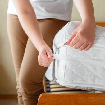 女性は整形外科用マットレスの角に新しいきれいなマットレスパッドを置きました。自宅のベッドリネン。シートは柔らかく清潔なマットレスに着用されています。寝室のインテリアの汚れで洗われたリネンマットレスパッドからの保護。平方。