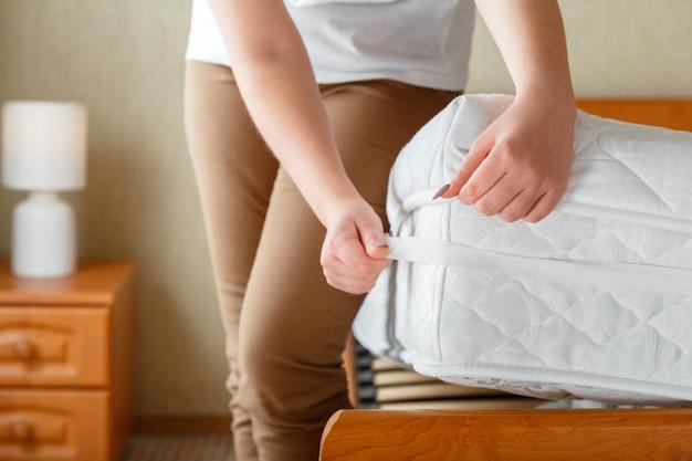 女性は整形外科用マットレスの角に新しいきれいなマットレスパッドを置きました。自宅のベッドリネン。シートは柔らかく清潔なマットレスに着用されています。寝室のインテリアの汚れで洗われたリネンマットレスパッドからの保護。