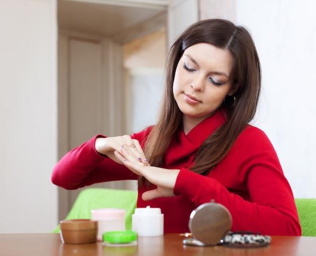 Woman puts cream on hands
