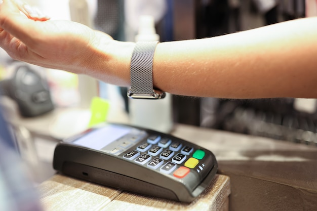 Woman puts hand with smart watch and pays contactless payment secure payment by bank terminal